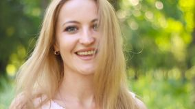 Retrato del primer hermoso sonriente de la mujer joven, contra el verde del parque del verano almacen de metraje de vídeo