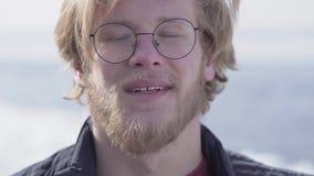 Retrato del primer del hombre barbudo hermoso en vidrios con el pelo rubio que mira en la cámara que sonríe al aire libre Ocio metrajes