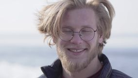 Retrato del primer del hombre barbudo hermoso en vidrios con el pelo rubio que mira en la cámara que sonríe al aire libre Ocio almacen de video