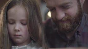 Retrato del primer del hombre barbudo que se sienta en la tabla en la cocina con su hija que cuenta el dinero r almacen de metraje de vídeo