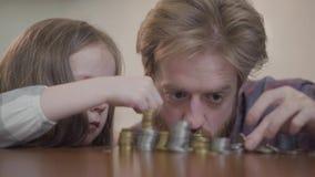 Retrato del primer del hombre barbudo que se sienta en la tabla en la cocina con su hija que cuenta el dinero r almacen de video