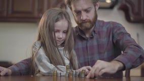 Retrato del primer del hombre barbudo que se sienta en la tabla en la cocina con su hija que cuenta el dinero r metrajes