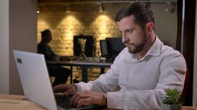 Retrato del primer del hombre caucásico adulto enfocado que mecanografía en el ordenador portátil en la oficina dentro metrajes