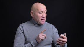 Retrato del primer del hombre caucásico adulto que tiene una conversación casual sobre el teléfono con el fondo aislado en negro metrajes