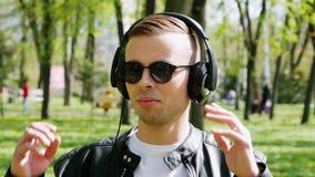 Retrato del primer del hombre caucásico atractivo, música que escucha en los auriculares almacen de metraje de vídeo