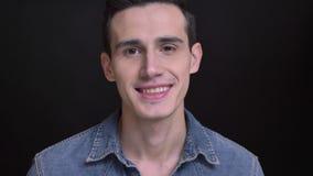 Retrato del primer del hombre caucásico joven que sonríe alegre y que mira la cámara con el fondo aislado en negro almacen de metraje de vídeo