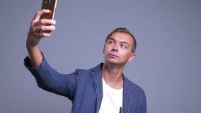 Retrato del primer del hombre caucásico joven que toma selfies en el teléfono con el fondo aislado en gris almacen de metraje de vídeo
