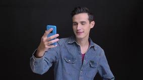 Retrato del primer del hombre caucásico joven que toma selfies en el teléfono con el fondo aislado en negro almacen de video