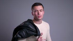 Retrato del primer del hombre caucásico masculino con la chaqueta de cuero sobre su hombro que mira la cámara y la presentación almacen de metraje de vídeo