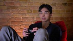 Retrato del primer del hombre coreano alegre joven que juega los videojuegos y la sentada sonriente en el puf dentro almacen de video
