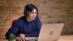 Retrato del primer del hombre coreano atractivo joven usando el ordenador portátil y poner sus auriculares almacen de video