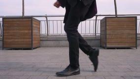 Retrato del primer del hombre de negocios afroamericano atractivo alegre joven que realiza un moonwalk en la calle en almacen de metraje de vídeo