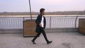 Retrato del primer del hombre de negocios afroamericano atractivo joven que camina y que baila alegre en la calle en almacen de video