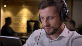 Retrato del primer del hombre de negocios caucásico alegre joven que escucha la música en los auriculares y que usa una tableta almacen de metraje de vídeo