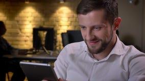 Retrato del primer del hombre de negocios caucásico alegre joven que mecanografía en la tableta y que sonríe en la oficina en lug almacen de video