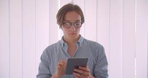 Retrato del primer del hombre de negocios caucásico hermoso joven en vidrios usando la tableta que se coloca dentro en la oficina metrajes