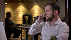 Retrato del primer del hombre de negocios caucásico joven que tiene una discusión sobre el teléfono que se sienta delante del ord almacen de metraje de vídeo