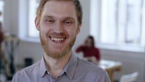 Retrato del primer del hombre de negocios europeo feliz joven de las finanzas que sonríe alegre en la cámara en lugar de trabajo  metrajes