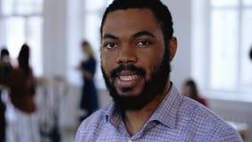 Retrato del primer del hombre de negocios negro barbudo sonriente feliz del CEO que presenta en la oficina de moda moderna Lugar  almacen de video