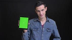 Retrato del primer del hombre hermoso caucásico joven usando la tableta y con confianza mostrar la pantalla verde a la cámara metrajes