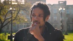 Retrato del primer del individuo afroamericano con los dreadlocks que fuman en fondo otoñal del campus almacen de video
