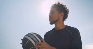 Retrato del primer del jugador de básquet de sexo masculino afroamericano atlético joven que lanza una bola en un aro al aire lib metrajes
