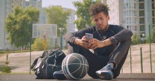 Retrato del primer del jugador de básquet de sexo masculino afroamericano fuerte joven que manda un SMS en el teléfono y que mira almacen de metraje de vídeo