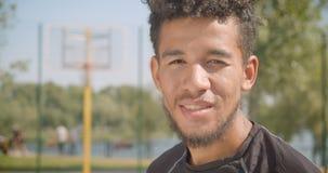 Retrato del primer del jugador de básquet de sexo masculino afroamericano hermoso joven que mira la cámara que sonríe feliz al ai almacen de video