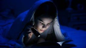Retrato del primer del libro de lectura adolescente de la muchacha debajo de la manta Fotografía de archivo libre de regalías