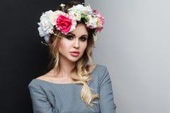 Retrato del primer del modelo de moda atractivo hermoso en vestido gris con las flores del maquillaje, del peinado y principales  foto de archivo