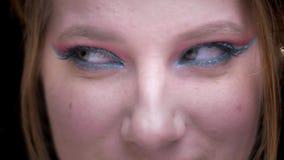 Retrato del primer del modelo de pelo rubio con el maquillaje colorido que se mueve los ojos hacia adelante y hacia atrás en fond metrajes