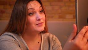 Retrato del primer del modelo femenino alegre gordo que habla en videochat en la tableta en atmósfera casera acogedora almacen de metraje de vídeo