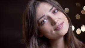 Retrato del primer del modelo femenino caucásico bonito joven que presenta delante de la cámara con las luces de la noche en almacen de video