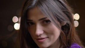 Retrato del primer del modelo femenino caucásico bonito joven que presenta delante de la cámara que mira misterioso adelante metrajes