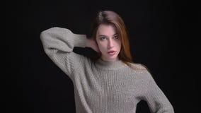 Retrato del primer del modelo femenino caucásico hermoso joven que fija su pelo y que presenta delante de la cámara almacen de metraje de vídeo