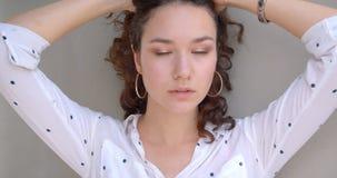 Retrato del primer del modelo femenino caucásico rizado de pelo largo bonito joven que presenta atractivo delante de la cámara co almacen de video
