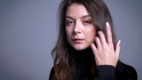 Retrato del primer del modelo femenino joven imponente que remete su pelo detrás del oído y que presenta delante de la cámara almacen de video