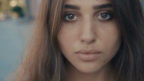 Retrato del primer del modelo moreno hermoso de la mujer joven que mira la cámara en un fondo de la calle de la ciudad Muchacha c metrajes