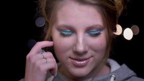 Retrato del primer del modelo rubio con el maquillaje colorido de moda que presenta en cámara en fondo borroso de las luces almacen de video