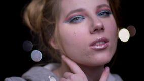 Retrato del primer del modelo rubio hermoso con el maquillaje colorido de moda que presenta en cámara en luces borrosas metrajes