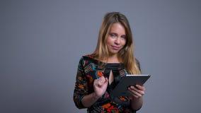 Retrato del primer del movimiento en sentido vertical femenino caucásico joven atractivo en la tableta que mira la cámara y la ri metrajes