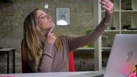 Retrato del primer del oficinista de sexo femenino hermoso que toma selfies atractivos en su teléfono en la oficina almacen de video