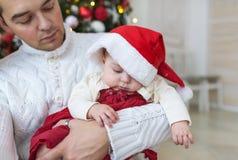 Retrato del primer del padre joven en la ropa blanca que detiene a su bebé recién nacido contra el árbol de navidad adornado del  Fotografía de archivo libre de regalías