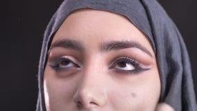 Retrato del primer del proceso de hacer maquillaje y de poner la fundación para la mujer musulmán joven en hijab en negro almacen de metraje de vídeo