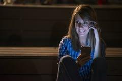 Retrato del primer que sonríe o que ríe a la mujer joven del freelancer que mira el teléfono que ve buenas noticias o las fotos c Foto de archivo libre de regalías