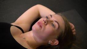 Retrato del primer del sportsgirl sudoroso y cansado que miente en el karrimat que es cansado y agotado en gimnasio metrajes