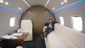Retrato del principal director del banquero del hombre joven que miente en el sofá durante el jet de la charla del teléfono en pr almacen de metraje de vídeo