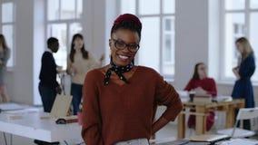 Retrato del profesional africano feliz joven del diseño, mujer de negocios alegre en lentes que sonríe en la oficina de moda almacen de metraje de vídeo