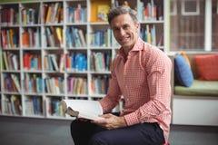 Retrato del profesor de escuela que sostiene el libro en biblioteca Imagen de archivo libre de regalías