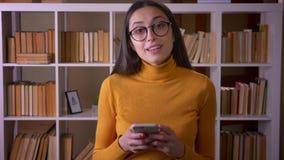 Retrato del profesor moreno hermoso en vidrios que mira en el smartphone atento que se coloca en la biblioteca metrajes